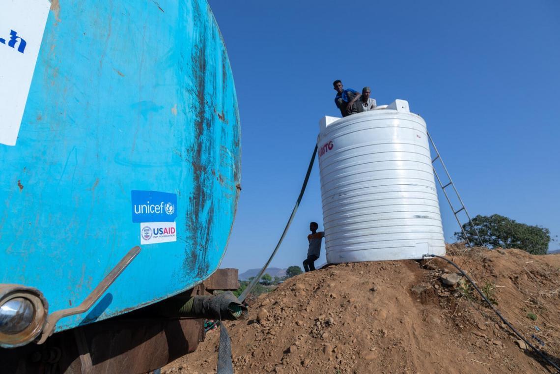 Etiopía. Dos personas se sientan encima de un tanque de agua en un lugar de desplazamiento.