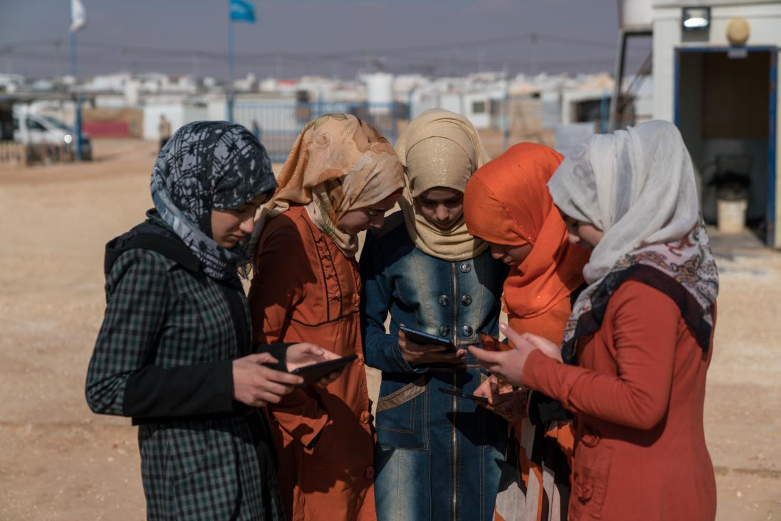 Five girls stand outside in a refugee camp, looking at cell phones and tablets.