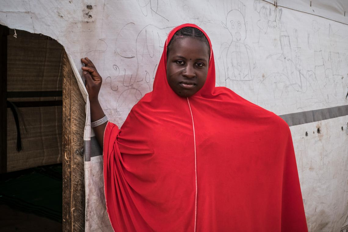 Nigerian refugee Hafsa Oumar, 16, stands outside a classroom.