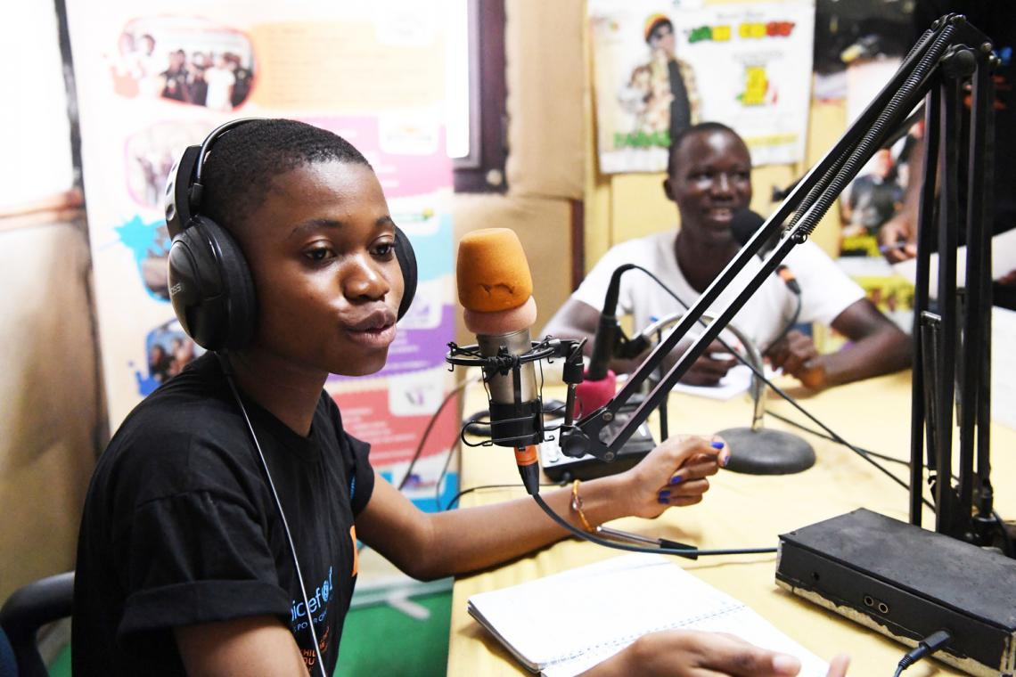 A 17-year-old girl in Côte d'Ivoire speaks into a microphone for a live radio programme.