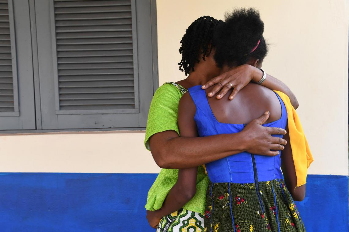 Mother gives her daughter a hug, Côte d'Ivoire.
