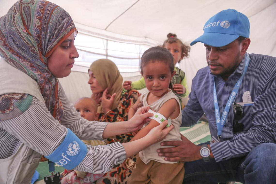 A UNICEF nutritionist screens children for malnutrition by measuring the upper arm circumference in Ain Issa camp, north eastern Syria.