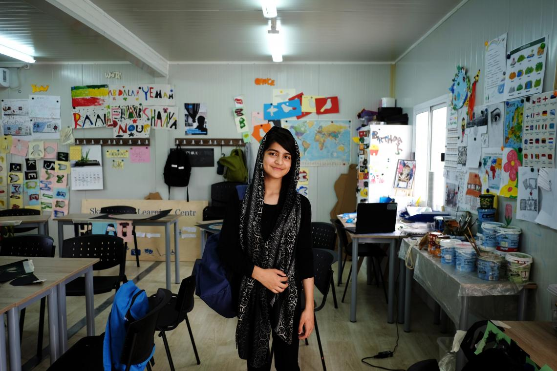 A teenage girl stands in a classroom for refugee and migrant children in Greece