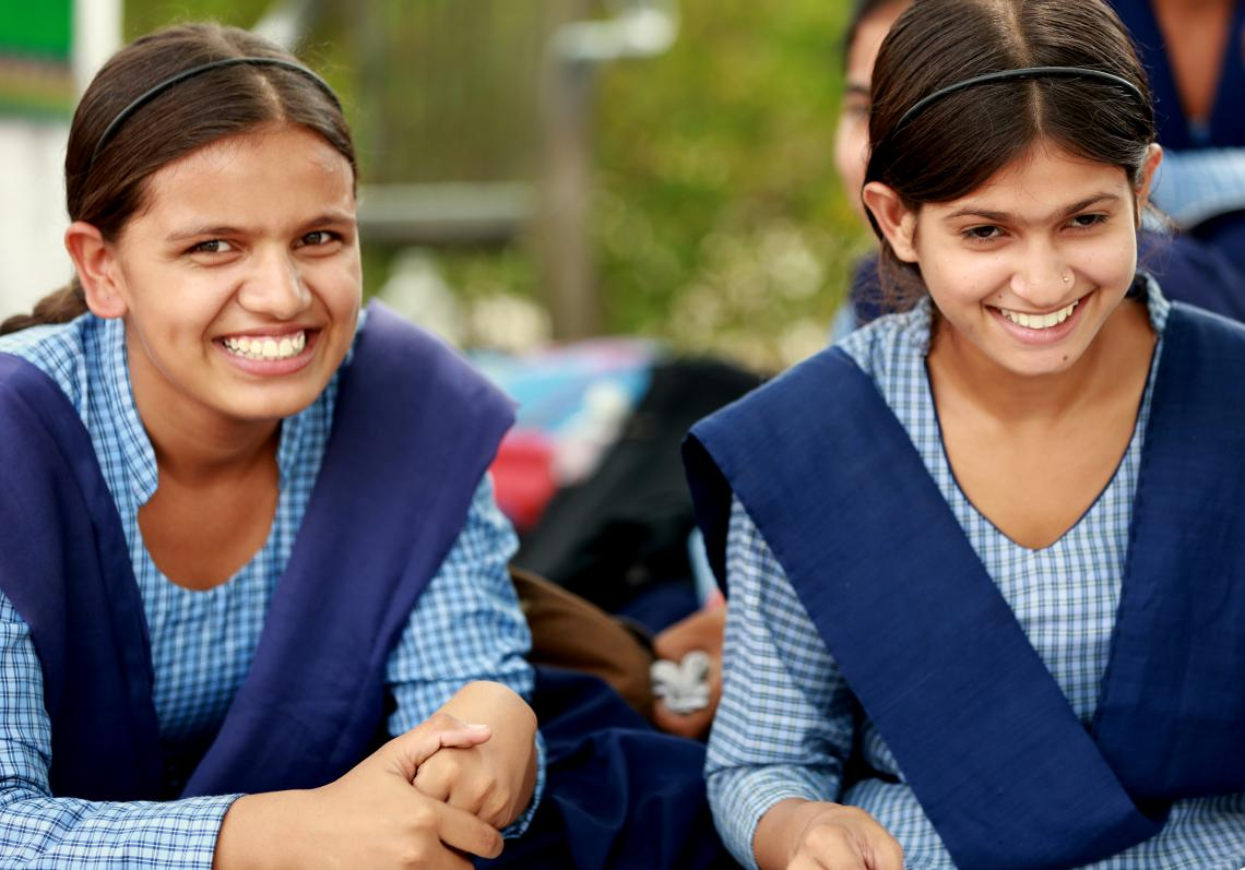 Two girls in school uniforms smile.