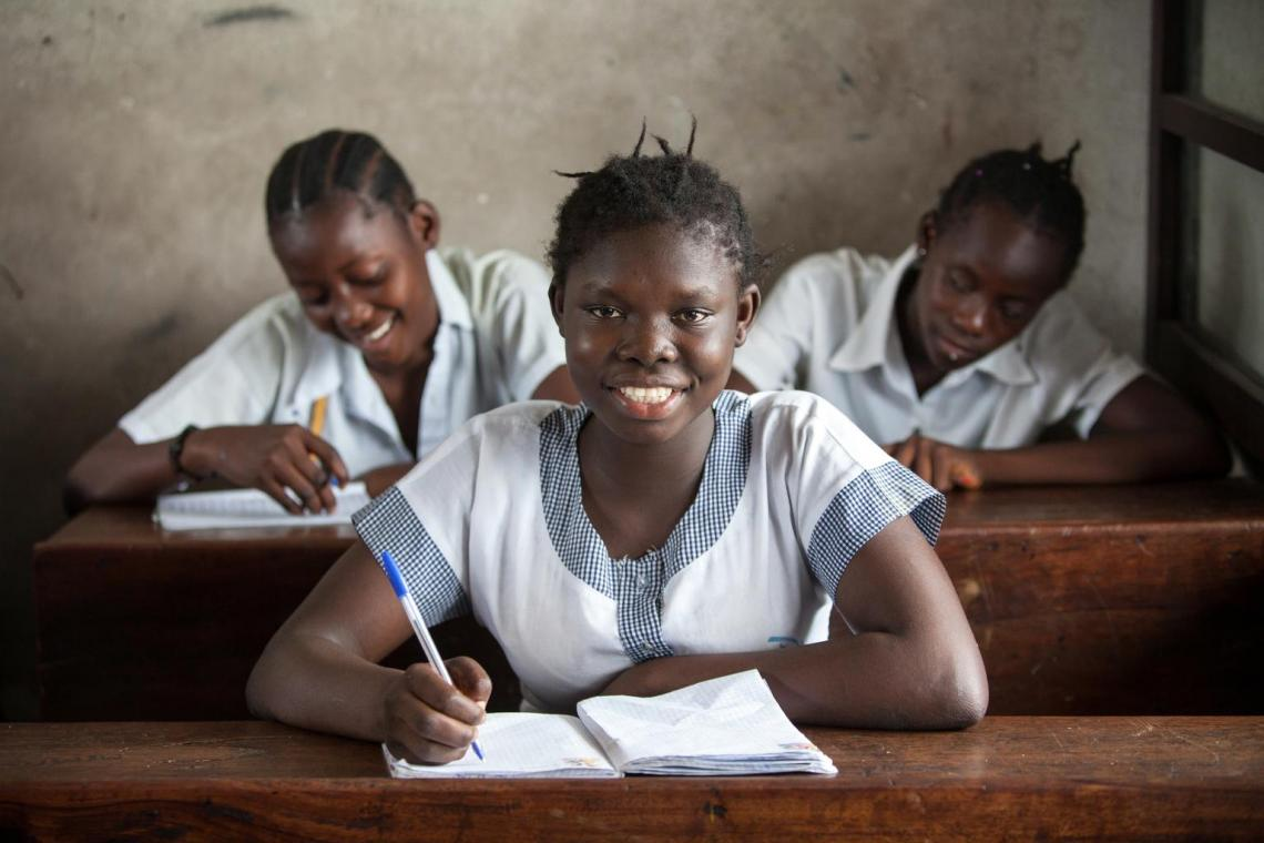 An adolescent girls sits at a school desk