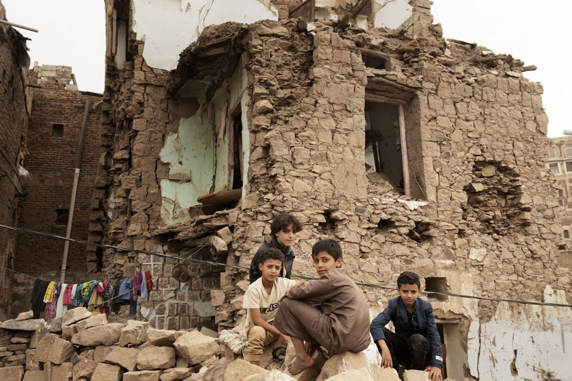 Yemen. Children sit in front of a damaged house inside the old city of Sana'a, Yemen.