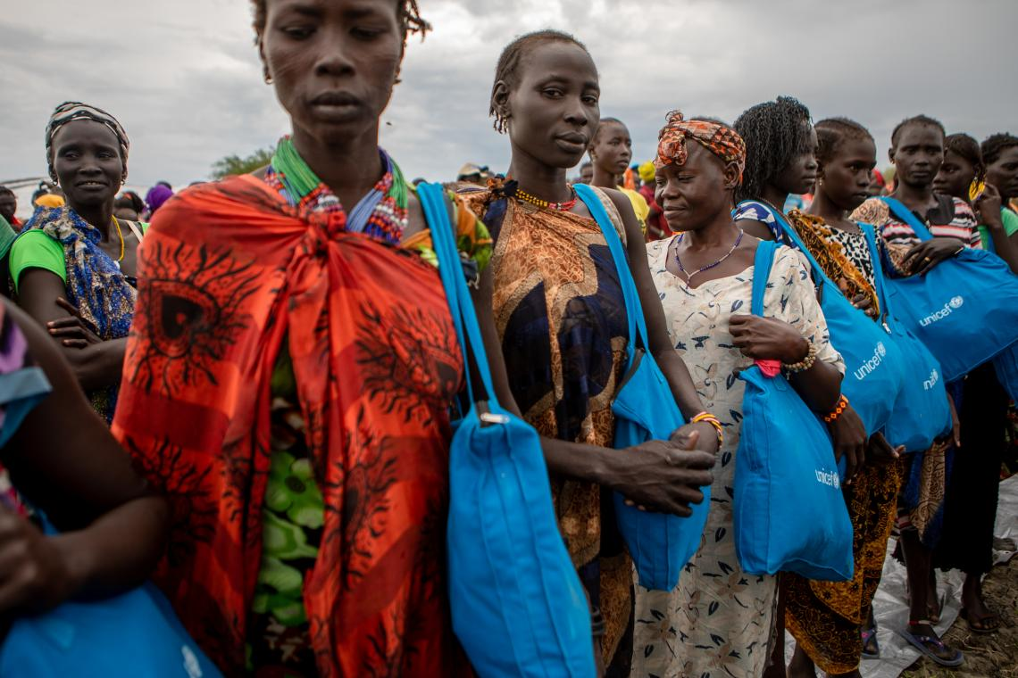 South Sudan. Women carry cloth bags containing feminine hygiene kits distributed by UNICEF. The kits include reusable, washable sanitary towels and soap.