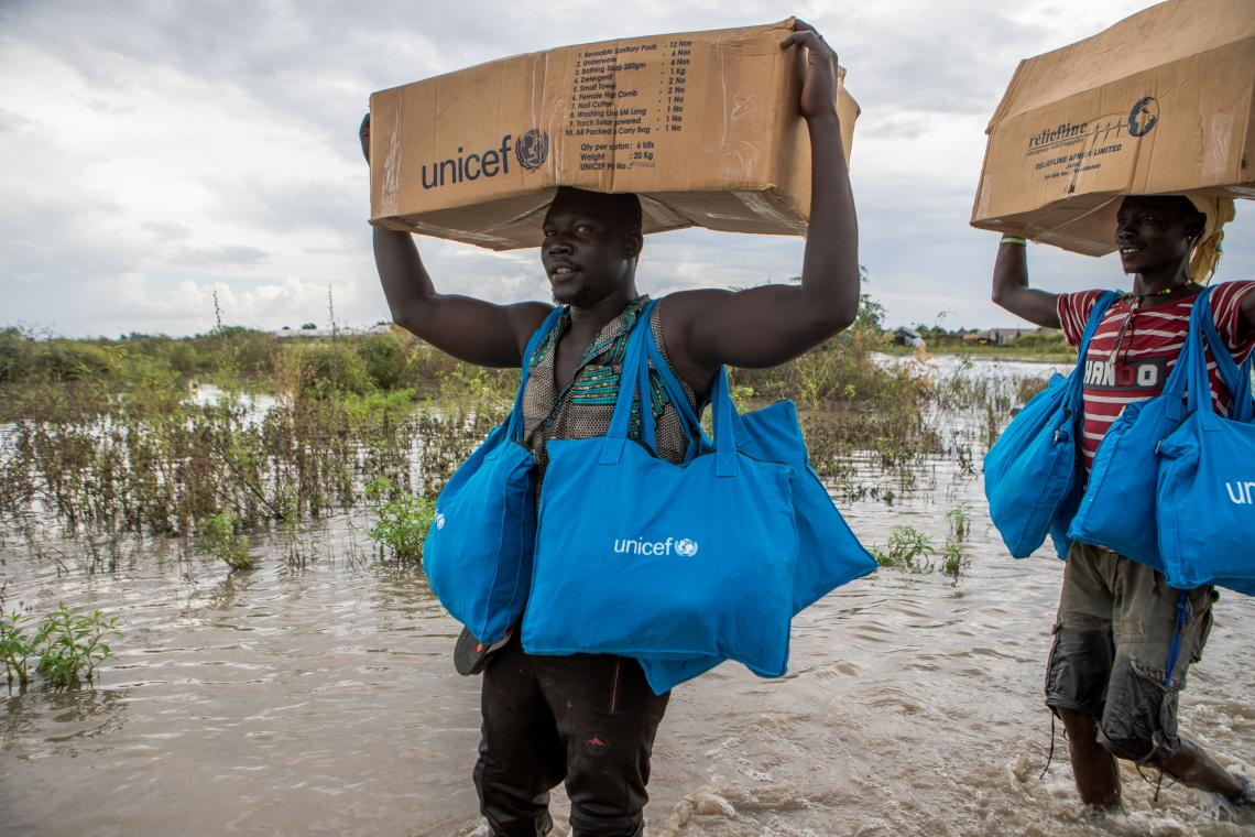 South Sudan. Aid teams wade through flood water to transport food and feminine hygiene kits to distribution points for displaced communities in Pibor.