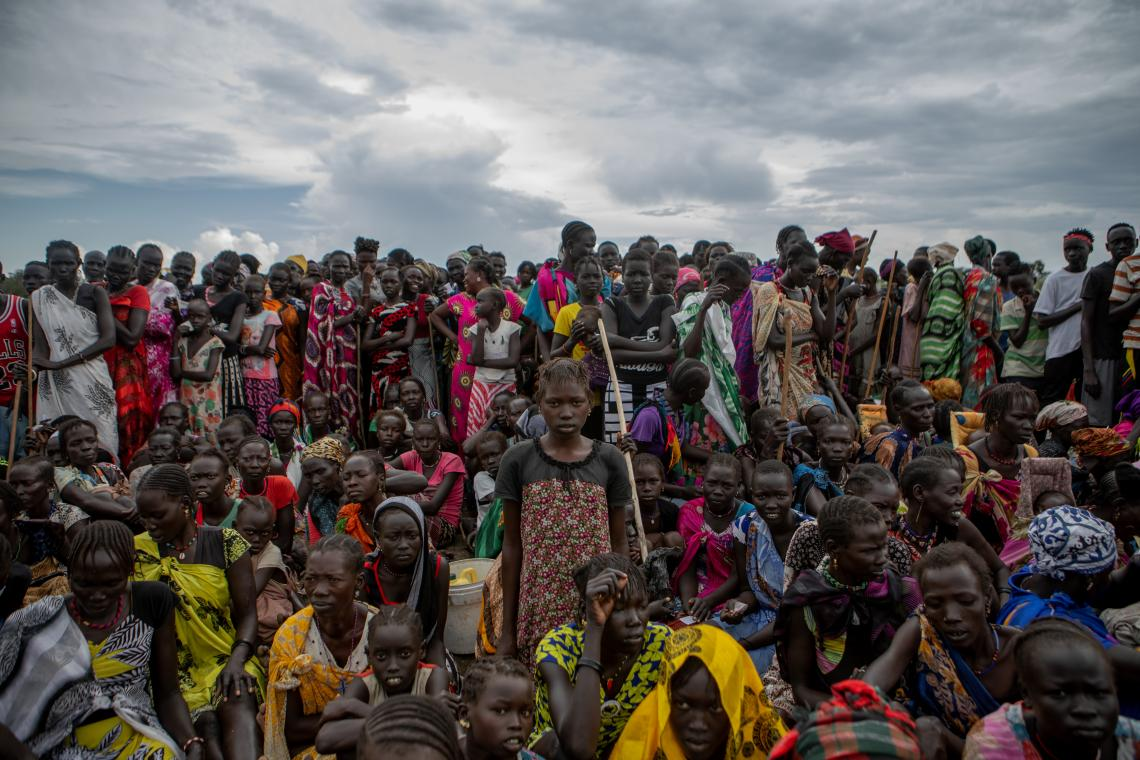 South Sudan. Families gather on a dry patch of ground waiting for relief items to be distributed in Pibor.