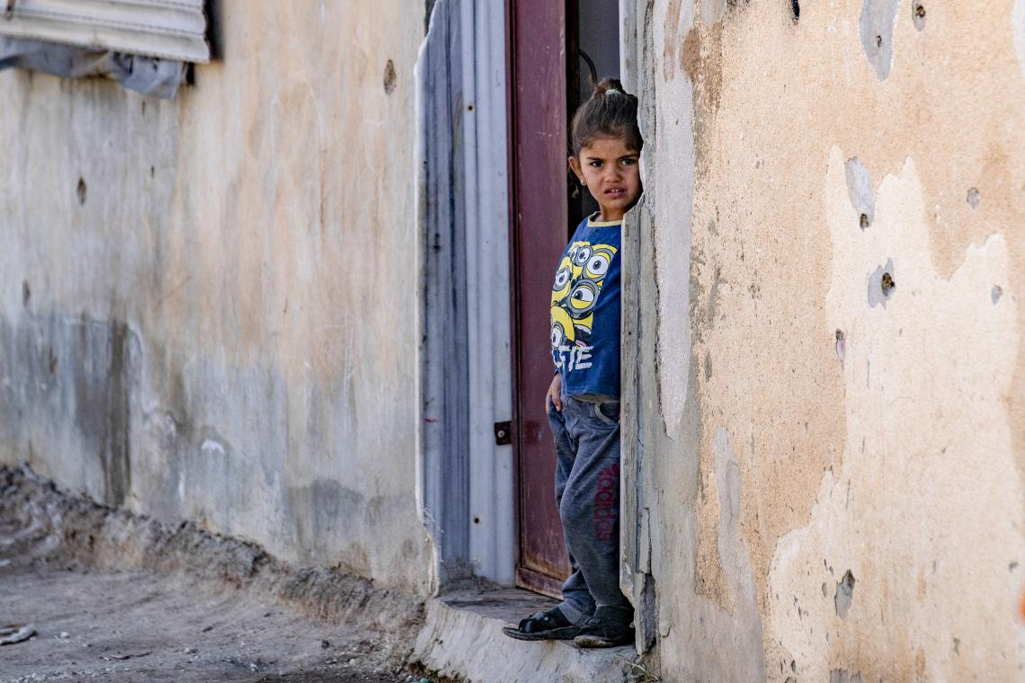 Syria. A girl stands in the doorway of a building in Al-Hasakeh, northeast Syria.