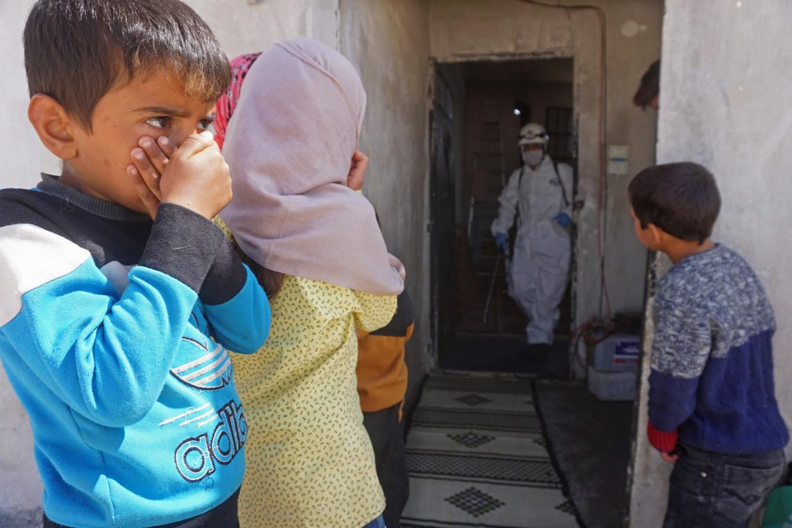 Children in Syria cover their mouths and noses as a member of the Syrian Civil Defence disinfects a former school building, now inhabited by displaced families, to prevent the spread of COVID-19.