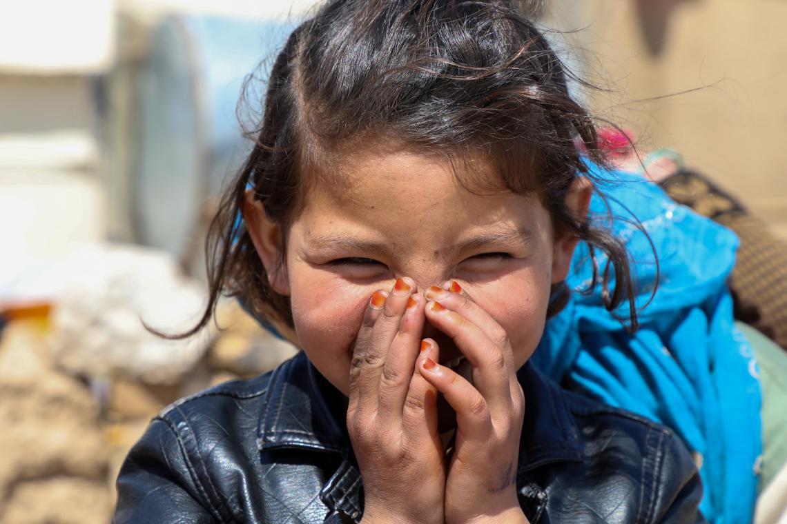 Afganistán. Una niña en un campo de desplazados sonríe a la cámara.