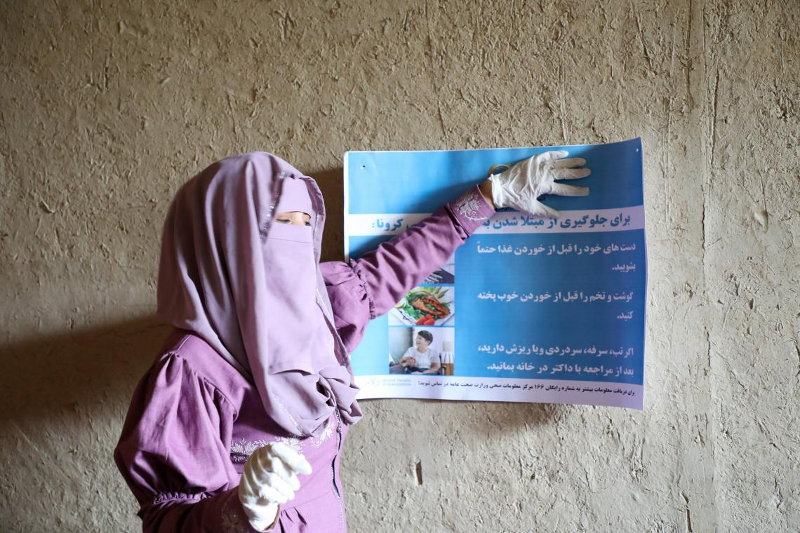 Afghanistan. A woman holds a sign with advice about COVID-19.