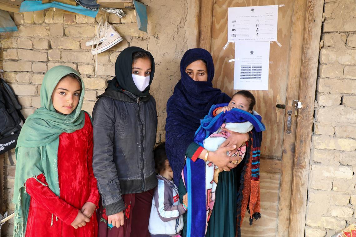 Afganistán. Una familia está parada afuera de un edificio en un campo de desplazados.