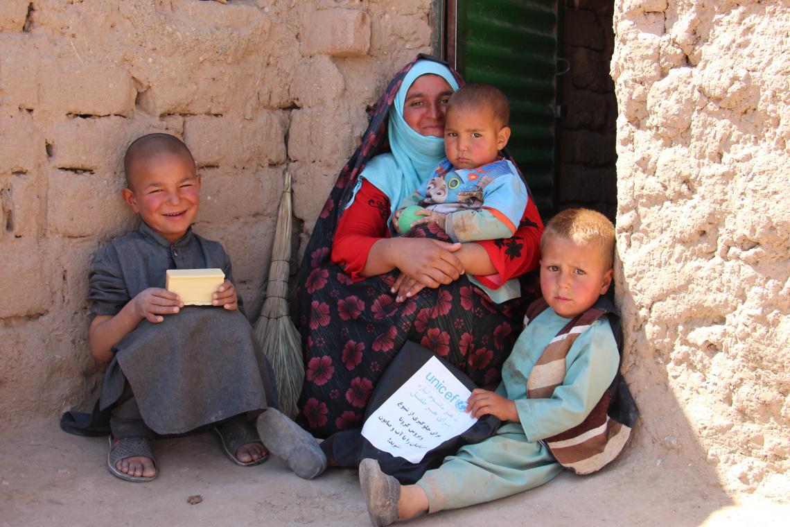 Afganistán. Una familia se sienta afuera de un edificio en un campo de desplazados.