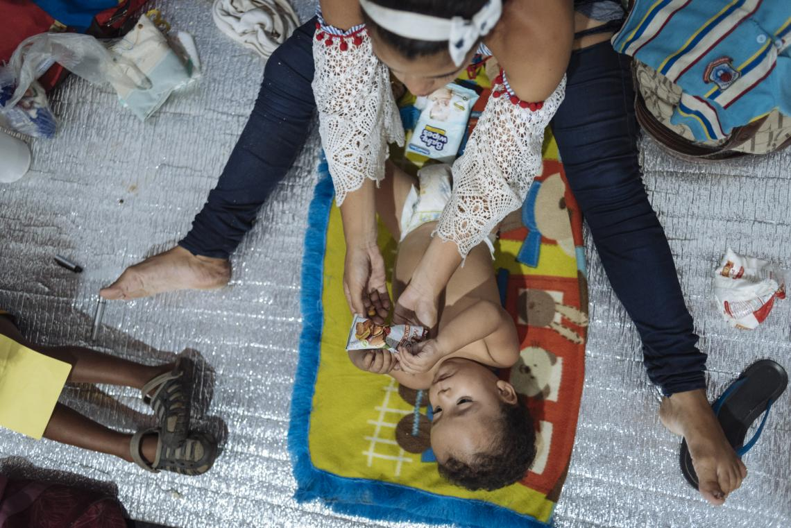 Colombia. A woman feeds her baby at an accommodation centre.