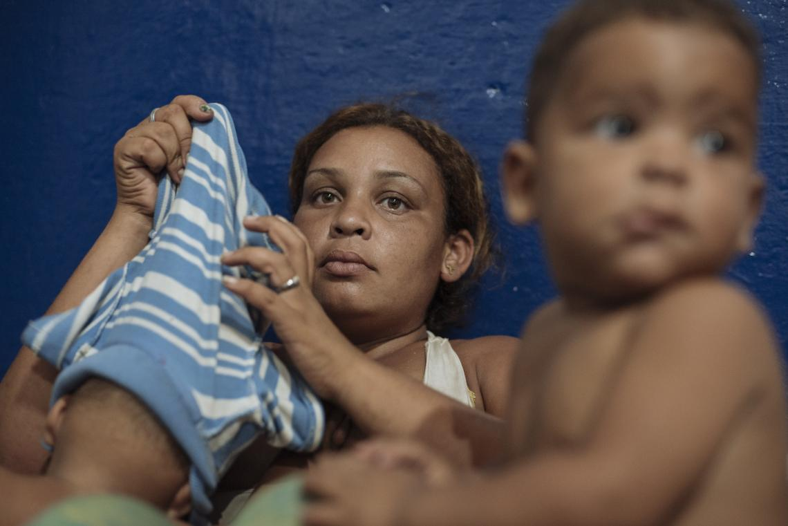 Colombia. A woman sits with her child at an accommodation centre.