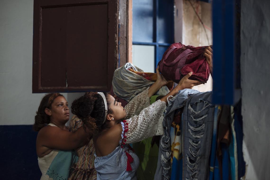 Colombia. A woman passes a bag over a wall at an accommodation centre.