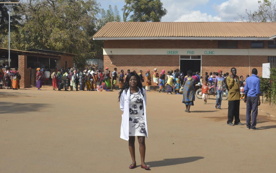 A woman stands in front of a health clinic, Malawi