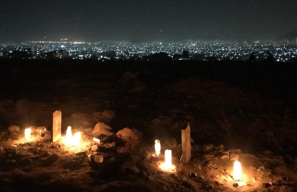 Candles sit on the graves of fallen students, Afghanistan