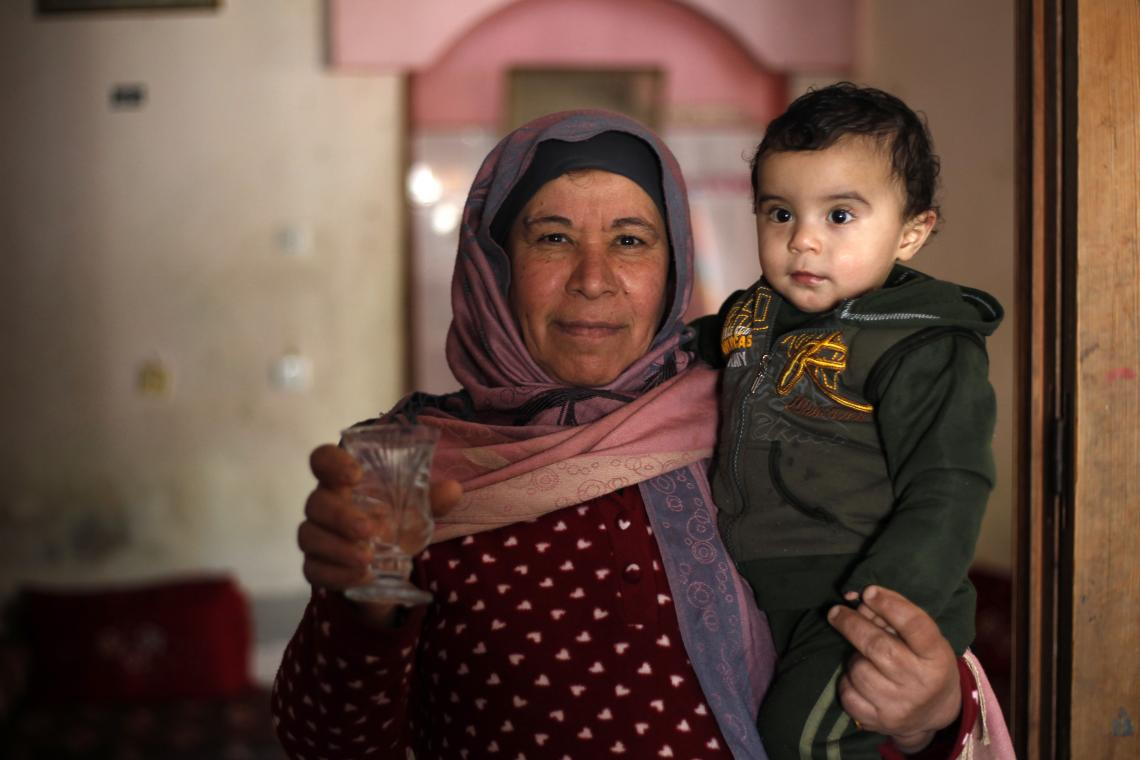A woman holds a child, Gaza