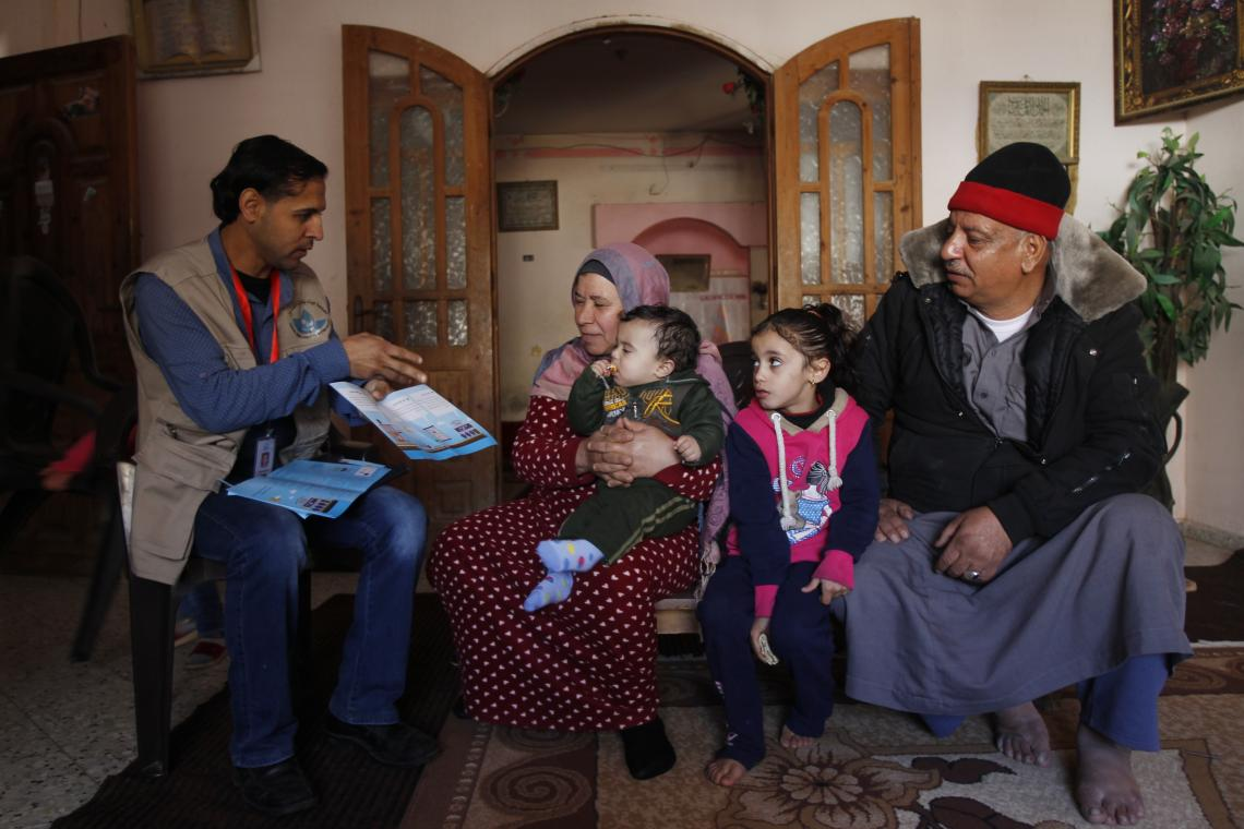 A Palestinian family listen to a member of Gaza's Coastal Municipalities Water Utility team