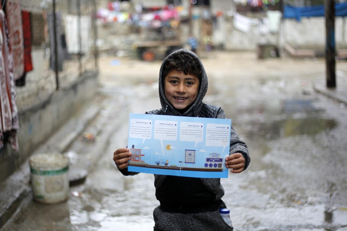 A Palestinian child holds up an information leaflet detailing how desalination works
