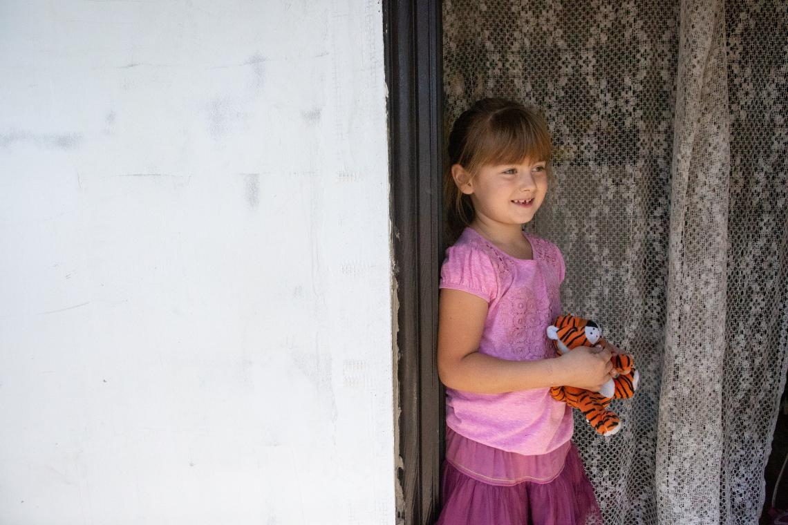 Ukraine. A girl stands in the doorway to her home.