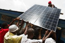 Residents carry a solar panel that will power a UNICEF-provided refrigerator at the Gbandiwlo Health Centre in the village of Gbandiwlo, in Kailahun District.
