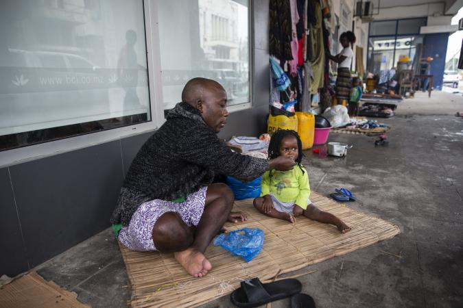Tome Raimundo feeds Teraza, a member of his family on 20 March 2019. They are living on the street after they were displaced from the informal settlement they were lived in Beira, Mozambique,