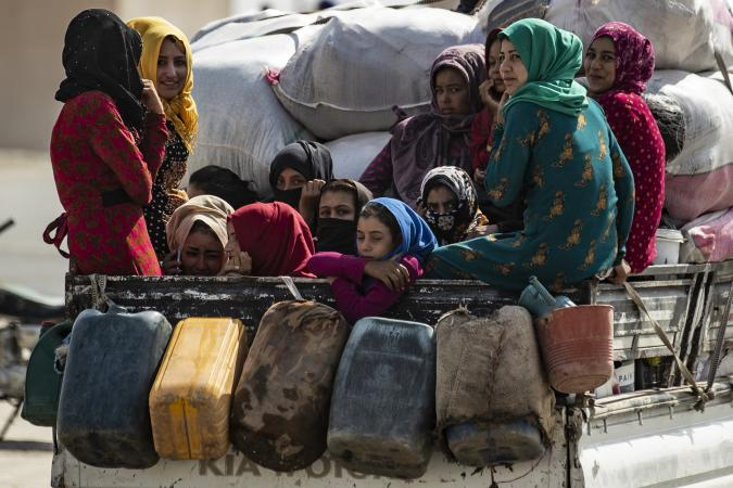 On 11 October 2019 in the Syrian Arab Republic, women and children are transported on the back of a truck as families displaced from Ras Al-ain arrive in Tal Tamer, 75km southeast Ras of Al-ain, having fled escalating violence.