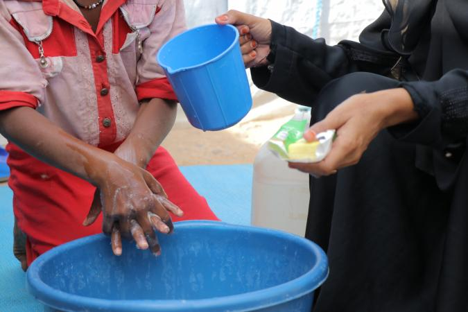 At a centre for families fleeing insecuirty, Esslam learns how to correctly handwash. She is being taught by Zahara a mother to mother peer educator, trained to spread health information and awareness, she also arrived in the IDP centre 3 years ago