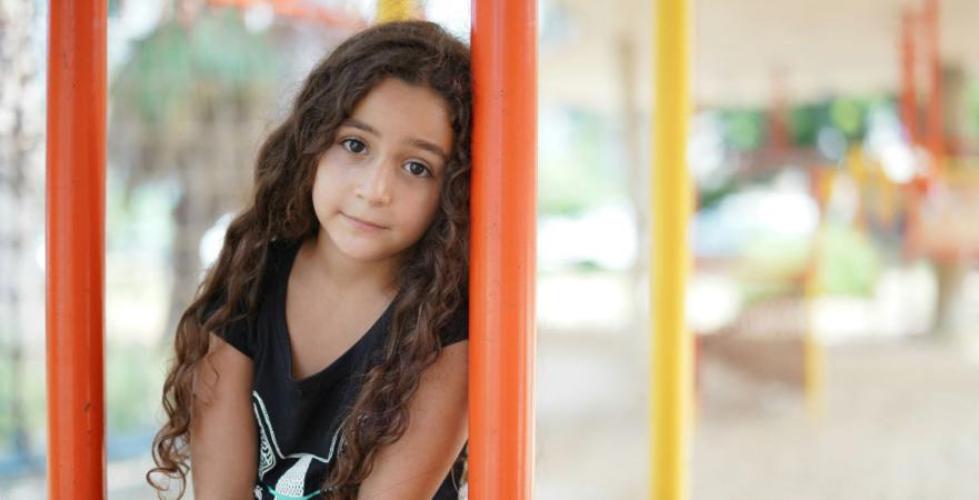 A young girl leans against a post
