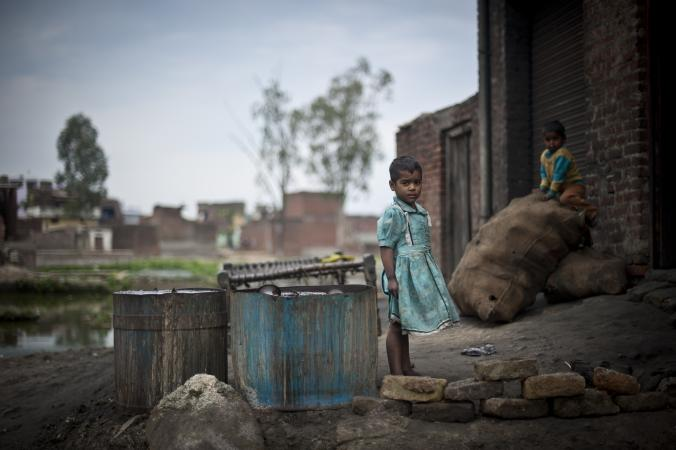 A young girl and boy play outside a metal polishing workshop in a slum in India.