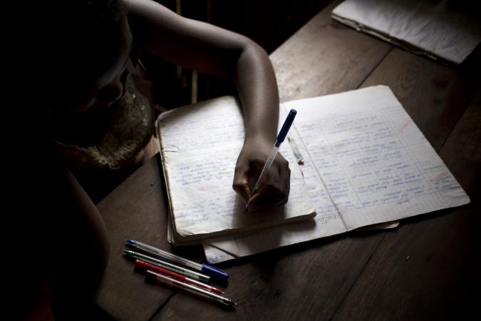 Young girl does her homework inside her family home in Madagascar