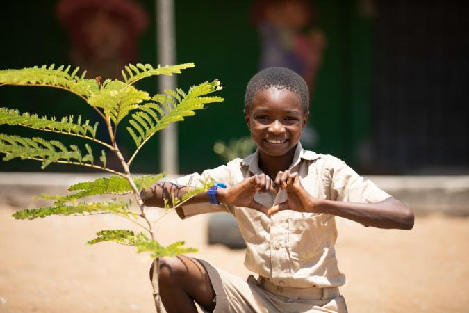 A boy makes a heart symbol with his hands in Côte d'Ivoire