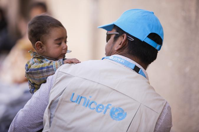 A UNICEF worker holds a child in his arms, Syrian Arab Republic