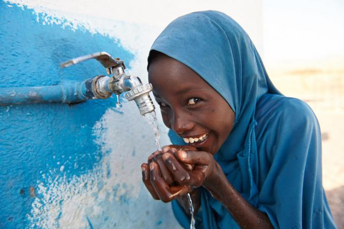 A girl child drinks safe water from a tap