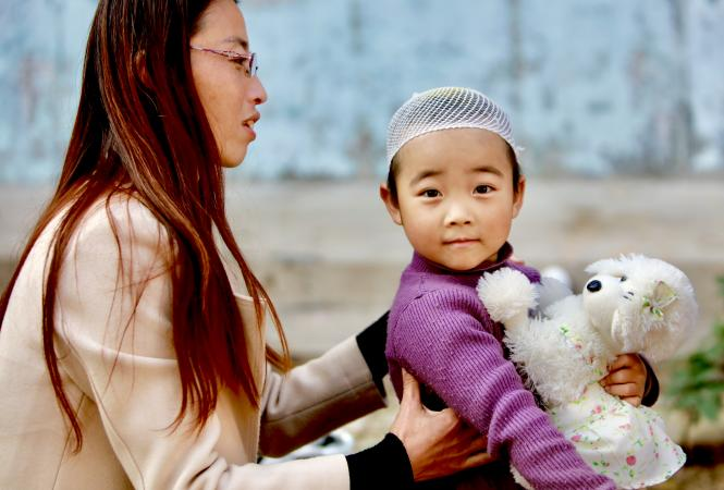A woman sits with a young child in China, in 2017.