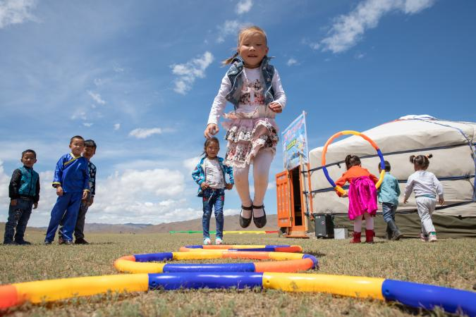 Children play outdoors at the newly opened mobile 'ger' (traditional nomadic tent) kindergarten in the Janjin bagh area, in Erdenetsogt soum in Bayankhongor Province, Mongolia.