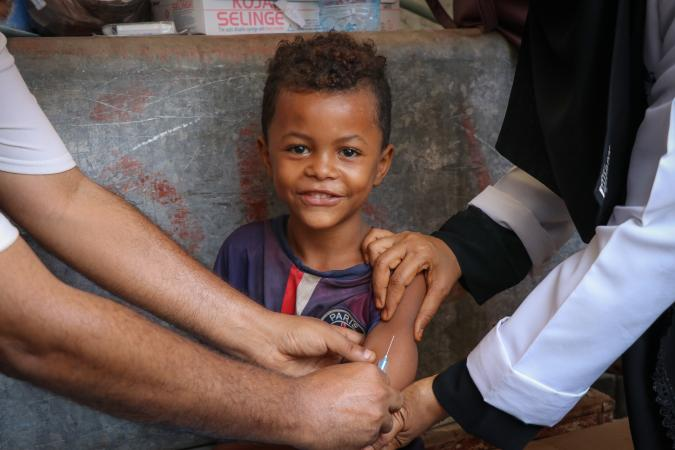 A child smiles while receiving a Measles and Rubella vaccination during a UNICEF-supported mobile vaccination campaign in Aden, Yemen on 9 February 2019.