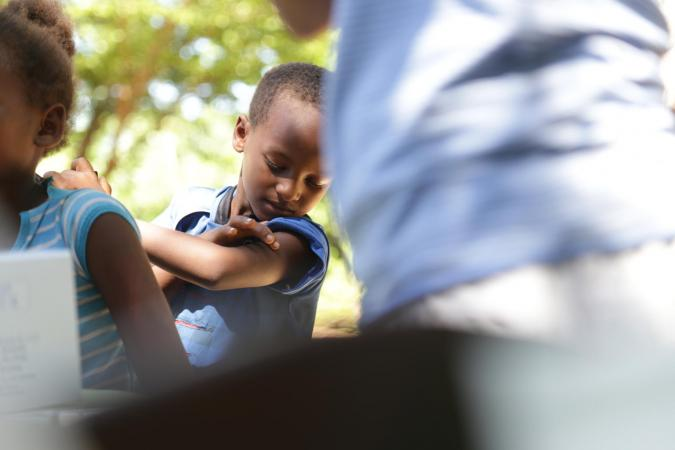 Madagascar. A boy checks his arm after receiving a vaccination.