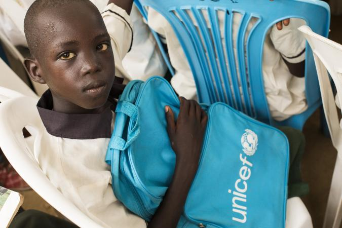 A young boy sits holding a UNICEF bag in South Sudan.