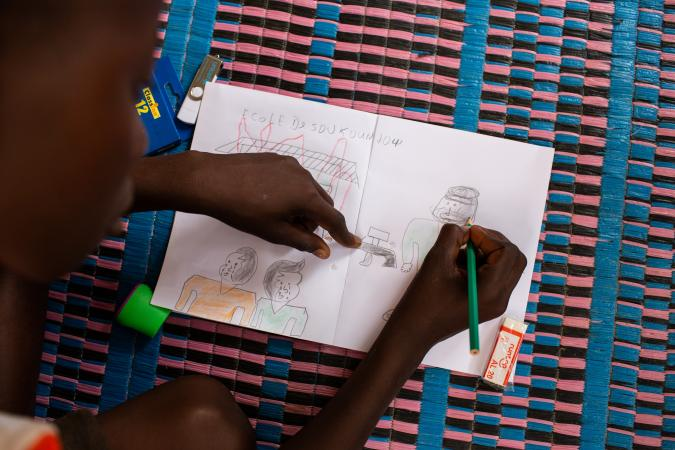 On 25 June 2019, in Dori, Burkina Faso, [NAME CHANGED] Hussaini, 14, draws pictures of the attack on his school in the village from which he and his family were forced to flee.