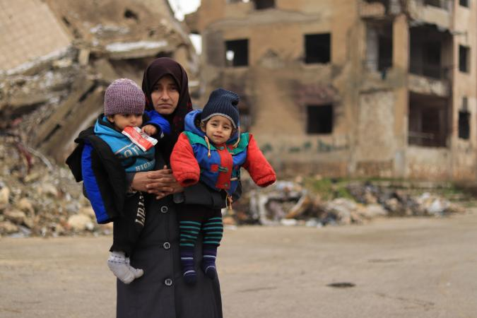 Syria. A woman holds her children.