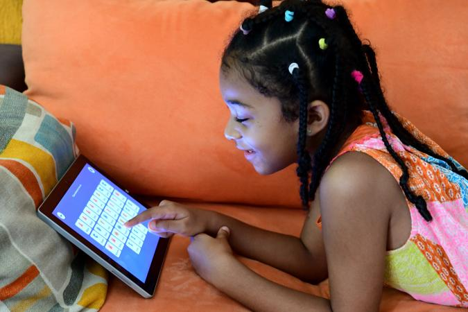 A seven-year-old girl in Côte d'Ivoire studies at home on a tablet device in 2020.