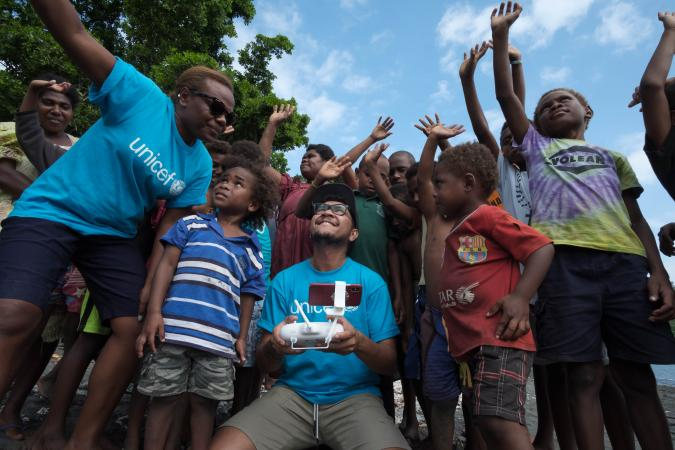 Jospeh Hing and Rebecca Olul show children of Epi how a drone works and explain how their community will take part in  the first trial of drone delivery of vaccines. Vanuatu