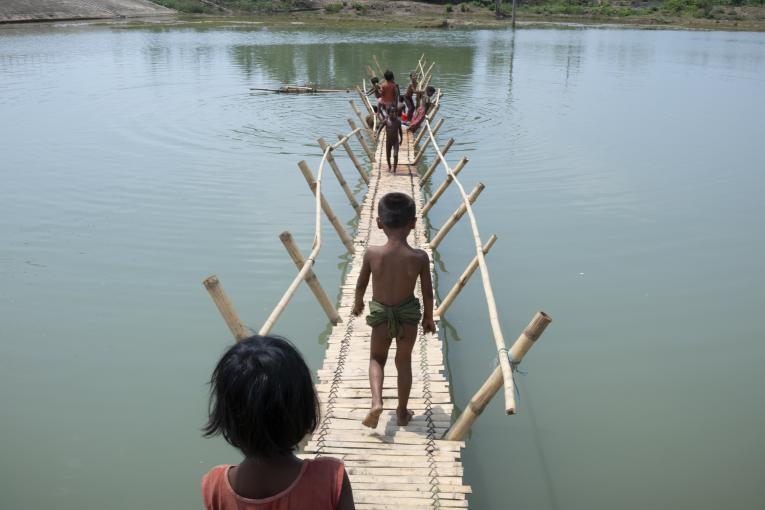 Rohingya children from Myanmar play on a bamboo bridge crossing a shallow body of water at high tide in Shamlapur refugee camp, Cox's Bazar District, Bangladesh on 19 April 2018.