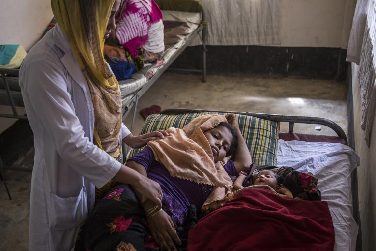 A midwife checks on exhausted new mother Hazera Begum, 18, who is recuperating next to her sleeping infant daughter, 3-day-old Kismat Ara, at the UNICEF-supported birthing centre in the Kutupalong camp for Rohingya refugees, in Cox's Bazar, Bangladesh. October 2017
