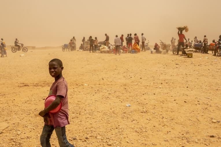 A boy in a red shirt with a plastic bowl crosses a dusty landscape with people lined up in the distance.